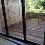 Glass patio doors leading to a wooden decking