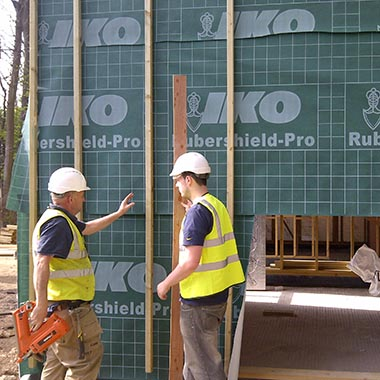Two construction workers checking a iko shield pro wall installation